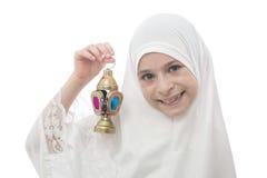 微笑的回教女孩在拿着赖买丹月灯笼的Hejab 库存图片
