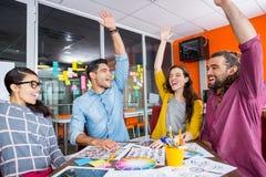 微笑的图表设计师用他们的手在会议一起上升了 免版税图库摄影
