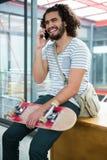 微笑的图表设计师谈话在手机 免版税库存照片