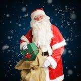 微笑的圣诞老人交付在一个大棕色袋子的礼物 免版税库存图片