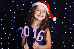 微笑的圣诞老人女孩与红色新年约会2016年 库存图片