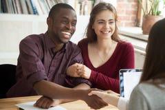 微笑的多种族夫妇顾客与经纪o握手 库存图片