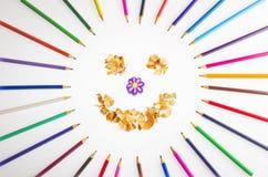 微笑的太阳从蜡笔和铅笔sharpenings安排了 免版税库存图片