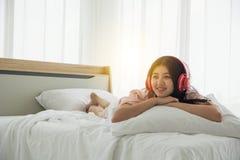 微笑的夫人画象桃红色睡衣的叫醒听到与耳机欢迎早晨光o的音乐 免版税库存照片