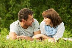 微笑的夫妇和位于在草outdoo 图库摄影
