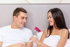 微笑的夫妇在与花的床上 库存图片