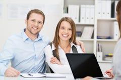 微笑的夫妇在与顾问的一次会谈 免版税库存图片