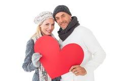 微笑的夫妇在冬天塑造摆在与心脏形状 免版税库存照片