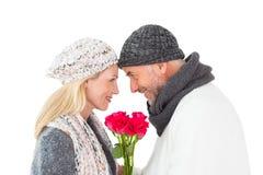 微笑的夫妇在冬天塑造摆在与玫瑰 免版税库存照片