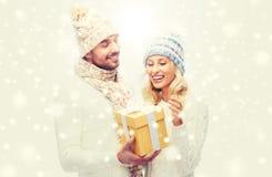 微笑的夫妇在冬天穿衣与礼物盒 库存照片
