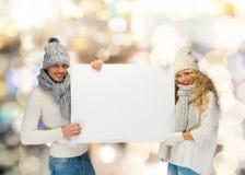 微笑的夫妇在冬天穿衣与空白的委员会 图库摄影