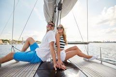 微笑的夫妇坐游艇甲板 免版税库存照片