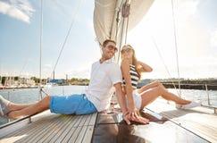 微笑的夫妇坐游艇甲板 库存照片