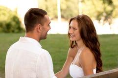 微笑的夫妇坐长凳在公园 库存照片