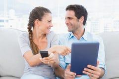 微笑的夫妇坐长沙发使用片剂个人计算机和观看的电视 库存照片
