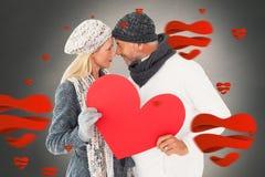 微笑的夫妇的综合图象在冬天塑造摆在与心脏形状 免版税库存图片