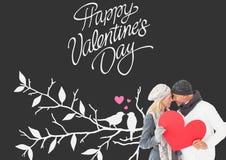 微笑的夫妇的综合图象在冬天塑造摆在与心脏形状 库存图片