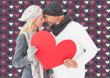 微笑的夫妇的综合图象在冬天塑造摆在与心脏形状 免版税库存照片