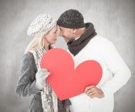 微笑的夫妇的综合图象在冬天塑造摆在与心脏形状 库存照片