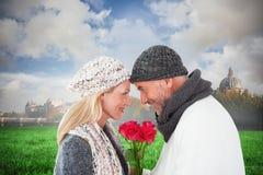 微笑的夫妇的综合图象在冬天塑造摆在与玫瑰 免版税库存图片