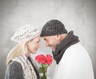 微笑的夫妇的综合图象在冬天塑造摆在与玫瑰 免版税库存照片
