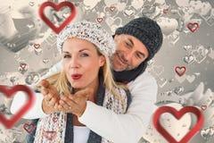 微笑的夫妇的综合图象在冬天塑造摆在 库存照片
