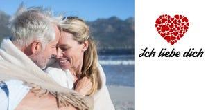 微笑的夫妇的综合图象坐海滩在毯子下 免版税库存图片