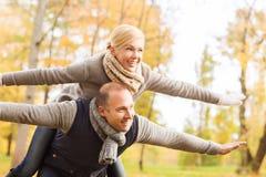 微笑的夫妇获得乐趣在秋天公园 图库摄影