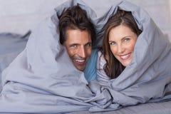 微笑的夫妇获得被包裹的乐趣在他们的鸭绒垫子 免版税库存照片
