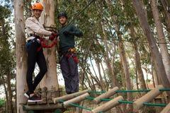 微笑的夫妇藏品在森林里用拉锁拉上线站立在木平台的缆绳 库存图片