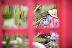 微笑的夫妇从事园艺的进行下去的金属结构 库存照片
