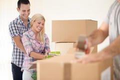 微笑的夫妇移动的房子 免版税库存照片