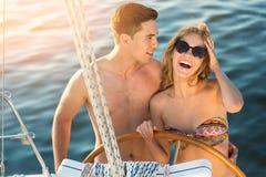 微笑的夫妇临近游艇轮子 图库摄影