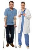 微笑的失去能力的人和女性医生Standing 免版税库存照片