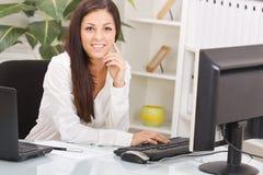 年轻微笑的女商人在办公室 库存照片