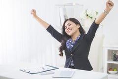 年轻微笑的女商人培养胳膊在完成她的工作以后 免版税库存图片