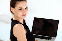 微笑的女商人画象有一台膝上型计算机的在办公室 免版税库存图片