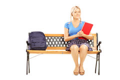 微笑的女学生坐一个长木凳和举行n 免版税库存照片