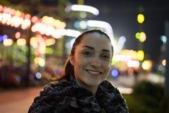 微笑的女孩与在背景的夜 免版税库存照片