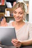 微笑的女孩使用Skype 图库摄影