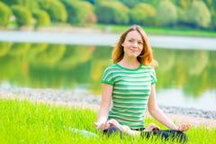 微笑的女孩信奉瑜伽者在一个绿色公园执行锻炼 免版税库存图片