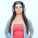微笑的女孩偶然佩带与耳机听音乐 免版税库存图片