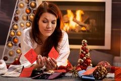 微笑的女孩决定圣诞节礼物 免版税图库摄影