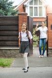 微笑的女孩出去房子后院对学校 免版税库存照片