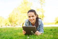 微笑的女孩压片说谎在草的个人计算机 免版税库存图片