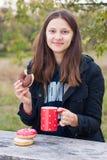 微笑的女孩吃油炸圈饼用在一张木桌上的咖啡 库存照片