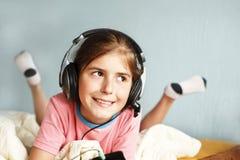 微笑的女孩听到音乐 库存图片