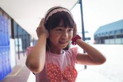 微笑的女孩听的音乐通过在走廊的耳机 免版税库存照片
