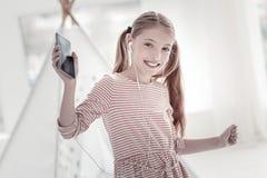 微笑的女孩听的音乐 图库摄影