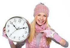 微笑的女孩在冬天给指向在时钟穿衣 免版税图库摄影
